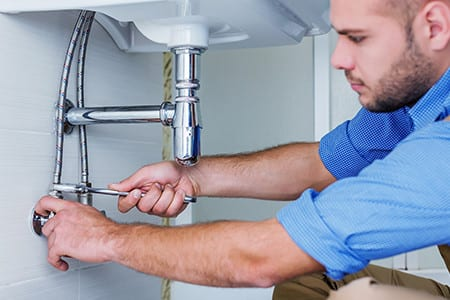 Plumber tightening up drain underneath sink to make sure no leaks
